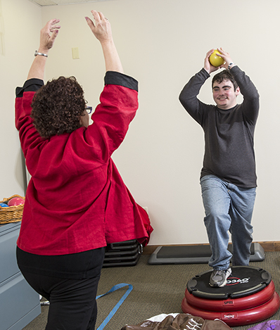 Adult is holding a small yellow ball over his head, smiling at the therapist making a similar stance