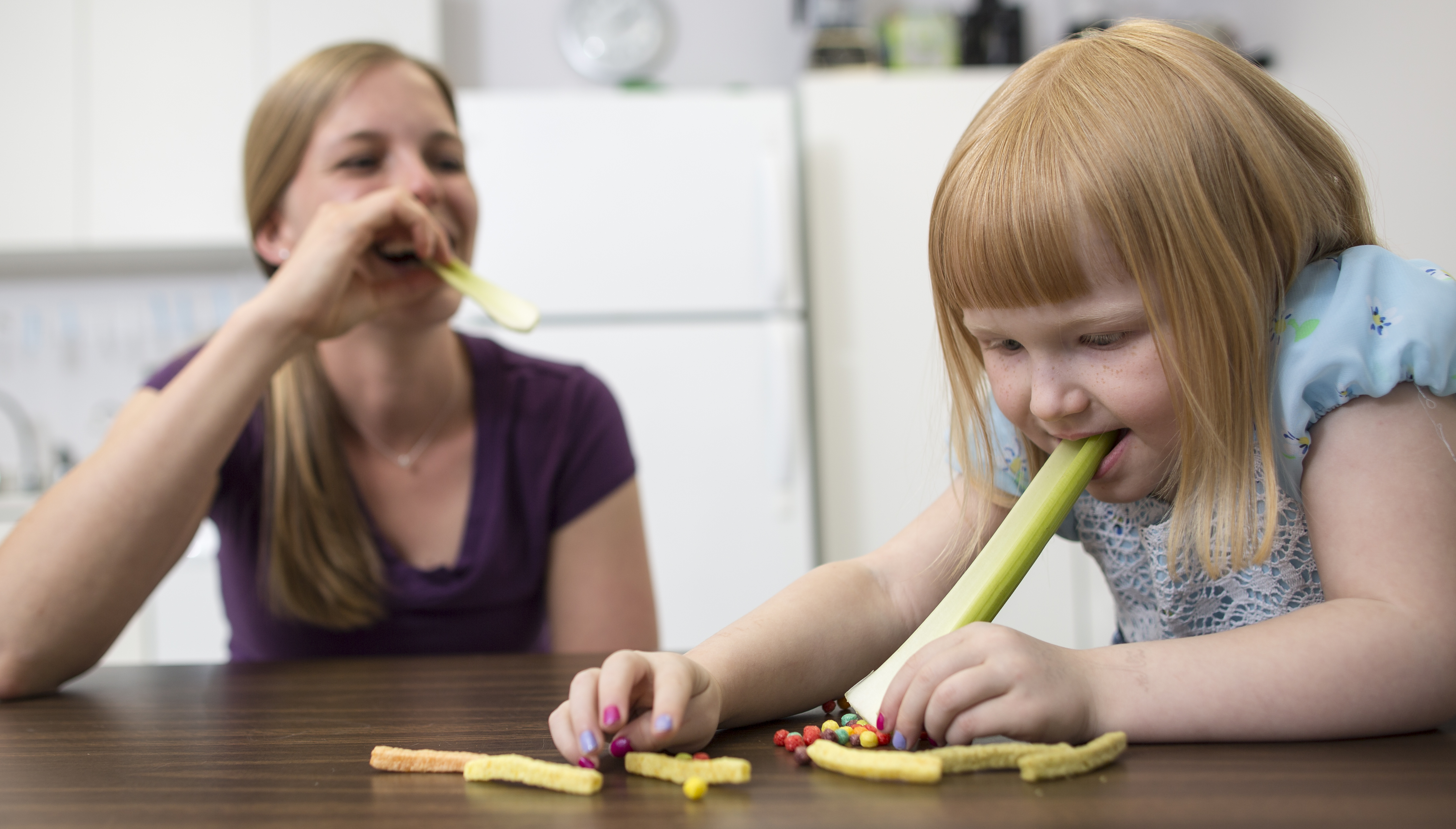 Child is sitting at the table with a long piece of celery in her mouth with the end touching the table. There are candy pieces and veggie straws on the table around her. A therapist is sitting next to her with a piece of celery in her mouth