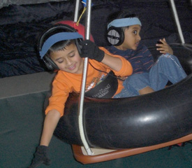 two children sitting in a tire swing together; each with headphones on