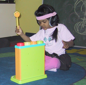 child sitting on the floor with a plastic mallet in her hand, playing with a toy