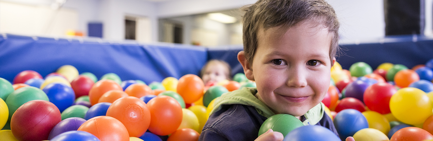 child in a ball bit, with colorful plastic balls up to his shoulders. He is looking at the camera with a smile.