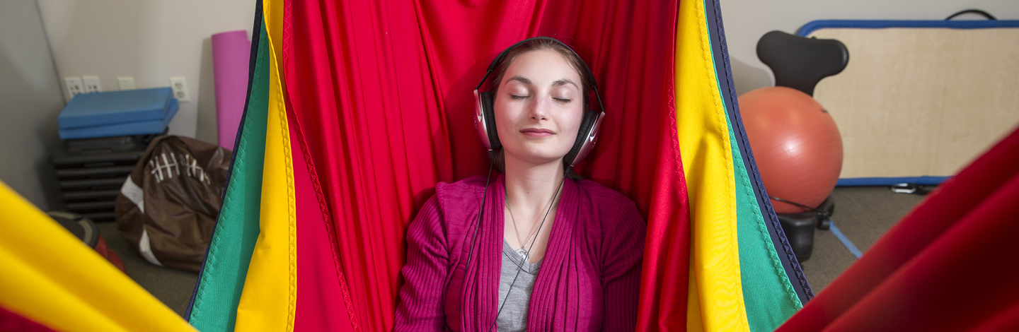 A young adult sitting in a colorful fabric hammock closing her eyes with headphones on