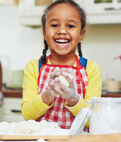 Young child is standing at the kitchen counter with flour and dough in front of her. She is smiling while holding ball of dough in her hands and flour on her face
